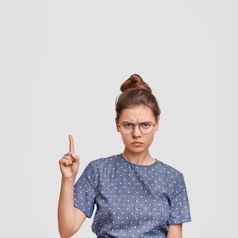Frau mit haaren in einem brötchen, das gepunktete bluse trägt