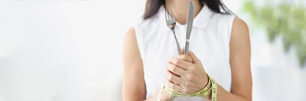 Frau mit händen mit maßband gefesselt, die gabel und messer nahaufnahme hält