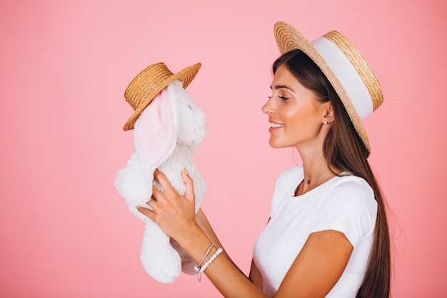 Frau mit häschenspielzeug auf rosa hintergrund