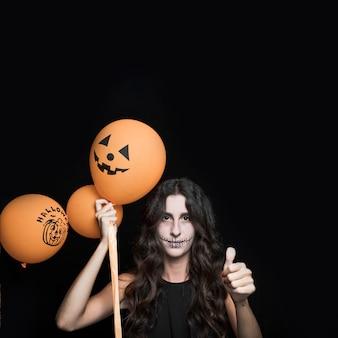 Frau mit halloween-ballonen, die gutes zeichen zeigen