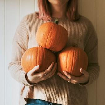 Frau mit halloween-kürbissen in einem bauernhaus