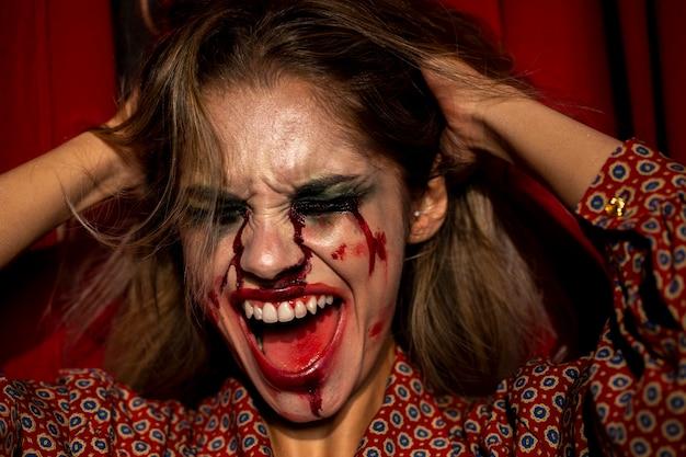 Frau mit halloween-spassvogelmake-up schreiend