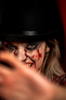 Frau mit halloween-spassvogelmake-uplächeln und betrachtet kamera