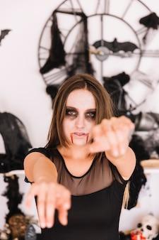 Frau mit halloween-zombie grimmig vor wand mit schlägern