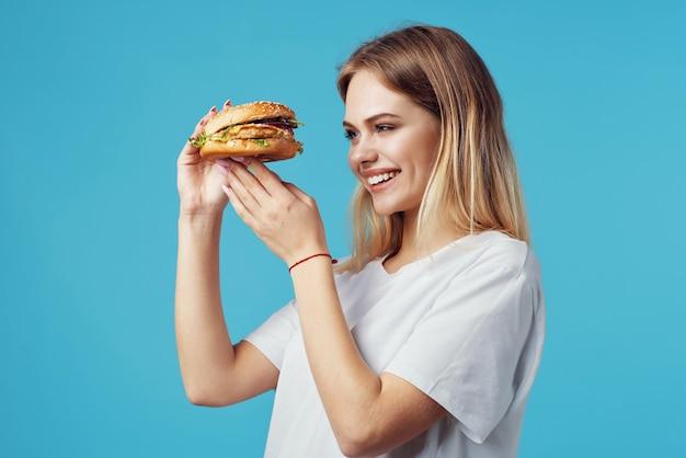 Frau mit hamburger-fast-food-liefersnackspaß blauem hintergrund
