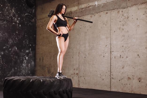 Frau mit hammer im fitnessstudio. mädchen mit vorschlaghammer im training