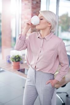 Frau mit hand in den taschen, die einen kaffee trinkt