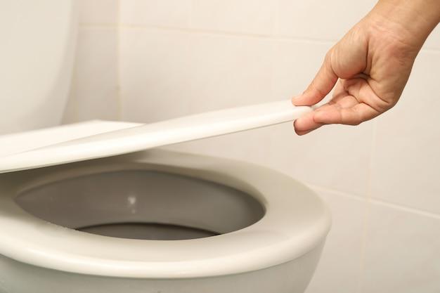 Frau mit hand zum öffnen des toilettendeckels