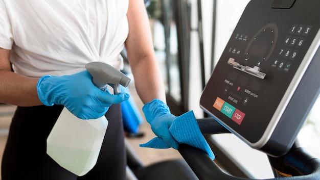 Frau mit handschuhen, die fitnessgeräte mit lösung reinigen