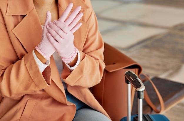 Frau mit handschuhen und gepäck am flughafen während der pandemie