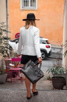 Frau mit handtasche und modischem hut