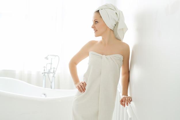 Frau mit handtuch auf kopf und körper nach dem duschen