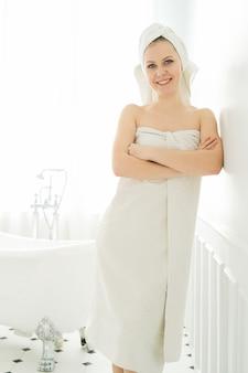 Frau mit handtuch auf kopf und körper nach der dusche