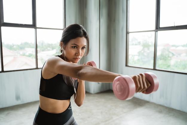 Frau mit hantel, die einige boxübung tut