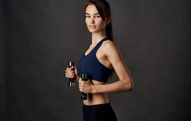 Frau mit hanteln fitness sport dunkle wand schlanke figur.
