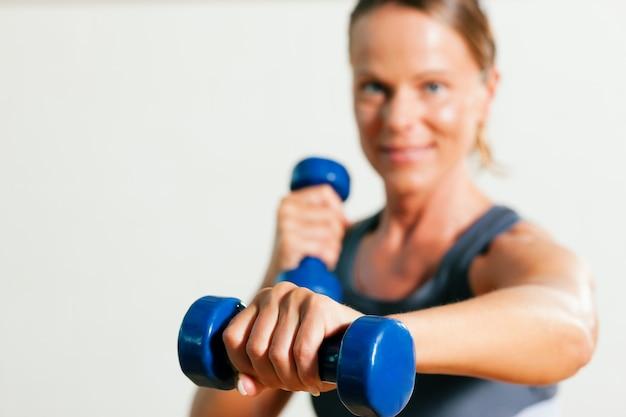 Frau mit hanteln im fitnessstudio