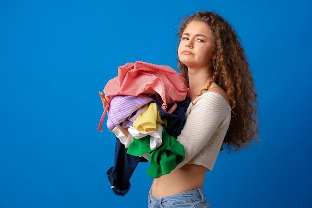 Frau mit haufen schmutziger wäsche vor blauem hintergrund
