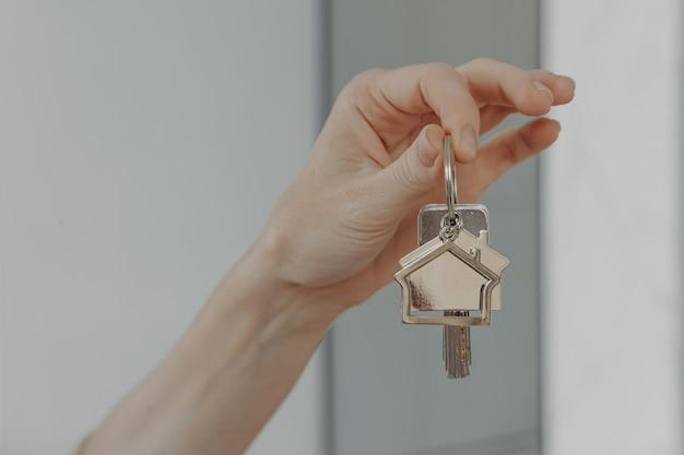 Frau mit hausförmigem schlüsselbund selektiver fokus auf weiblicher hand mit schlüssel aus neuem zuhause