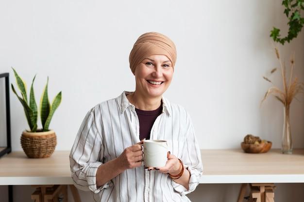Frau mit hautkrebs, die eine tasse hält