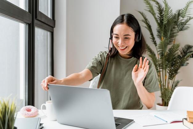 Frau mit headset, die videoanruf auf laptop hat
