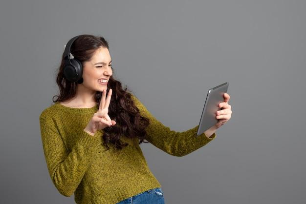 Frau mit headset und tablet in der hand, die spiele spielt und mit freunden online spricht, modernes unterhaltungskonzept