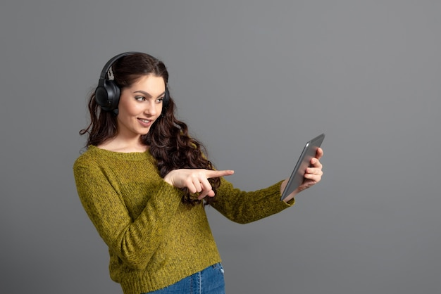 Frau mit headset und tablet in der hand, die spiele spielt und mit freunden online spricht