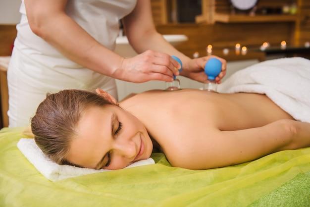 Frau mit heißem glas vakuum schröpfen massage im spa-zentrum