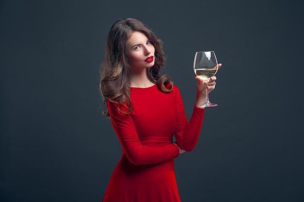 Frau mit hellem make-up, frisur, die rotes kleid trägt, das mit glas weinstock über dunkelheit aufwirft