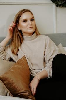 Frau mit hellem make-up und strengen gesichtszügen gekleidet in beigem pullover, der auf bett sitzt