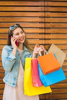 Frau mit hellen Einkaufstaschen sprechend telefonisch an der hölzernen Wand