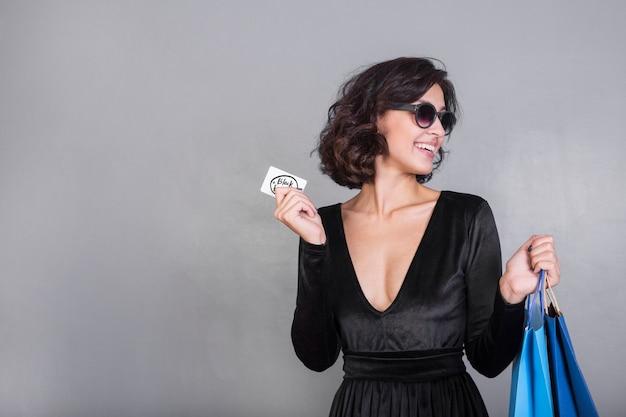 Frau mit hellen einkaufstaschen und kreditkarte