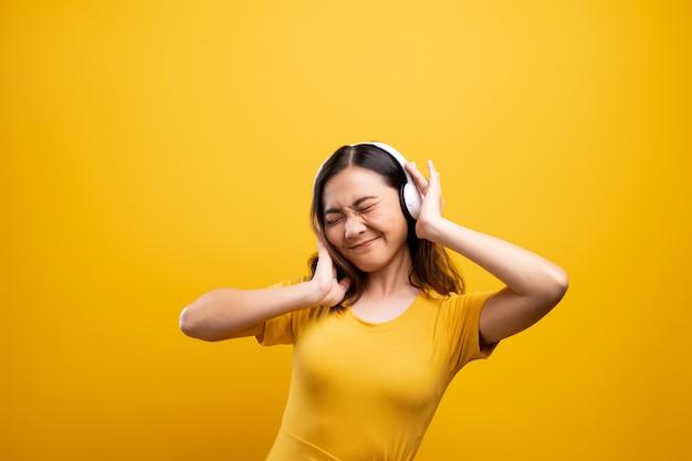 Frau mit hörender musik der kopfhörer auf getrenntem gelbem hintergrund