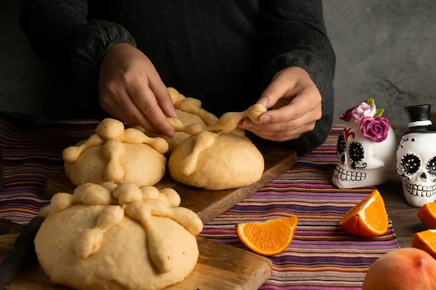 Frau mit hohem winkel, die pan de muerto-teig zubereitet
