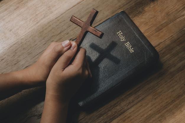 Frau mit holzkreuz in den händen, die um segen von gott auf altem bibelbuch betet