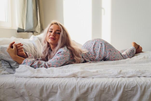 Frau mit honigblonden haaren, die dessous in einem boudoir-schlafzimmer in verschiedenen posen tragen.