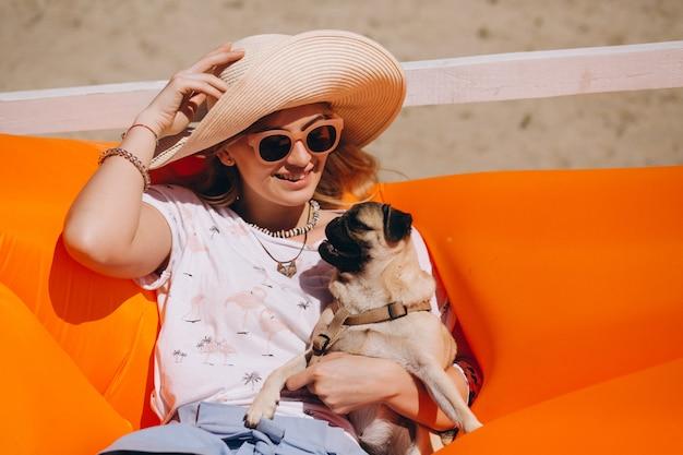 Frau mit hund am strand auf einer poolmatratze