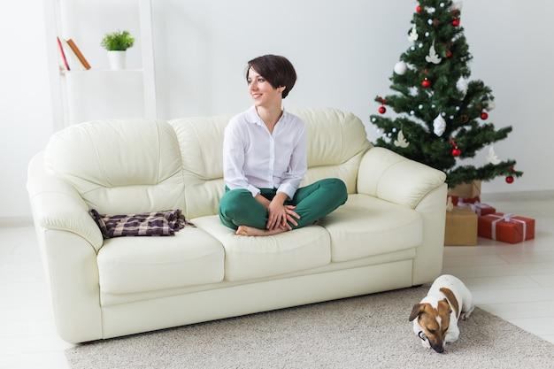 Frau mit hund im wohnzimmer mit weihnachtsbaum
