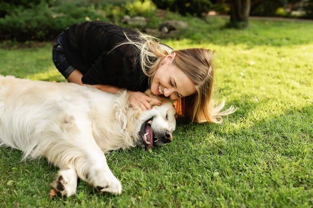 Frau mit hund labrador, der spaß im grünen park hat