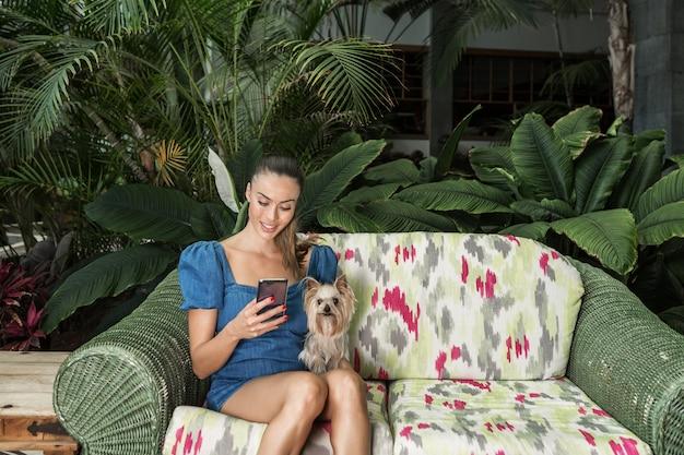 Frau mit hund unter verwendung des smartphone auf sofa