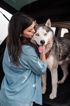 Frau mit husky-hund, der mit dem auto reist