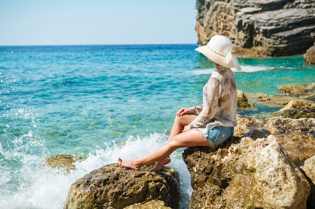 Frau mit hut, der auf felsen am strand sitzt