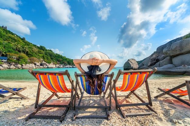 Frau mit hut, der auf stühlenstrand im schönen tropischen strand sitzt. frau, die auf einem tropischen strand bei koh nangyuan insel entspannt