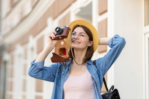 Frau mit hut, die im urlaub fotos macht