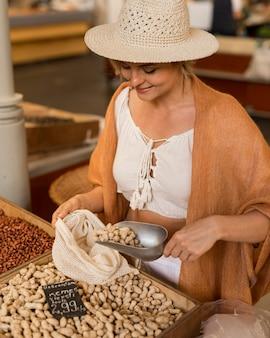 Frau mit hut, die trockenfutter am marktplatz nimmt