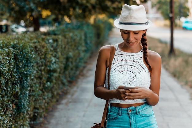 Frau mit hut gehend und ein intelligentes telefon in der straße an einem sonnigen sommertag verwendend