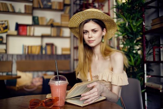 Frau mit hut sitzt im café zastava glas mit getränk restbuch.