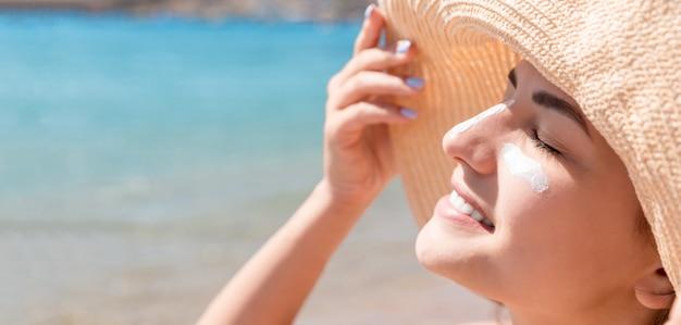 Frau mit hut trägt sonnencreme unter ihren augen auf