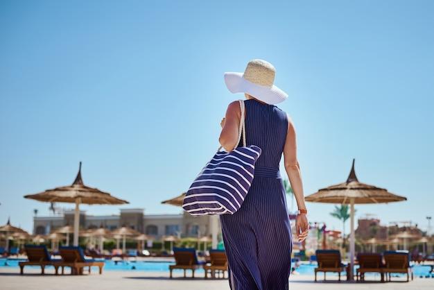 Frau mit hut und blauem kleid gehen im hotelresort in der nähe des swimmingpools mit strandtasche spazieren