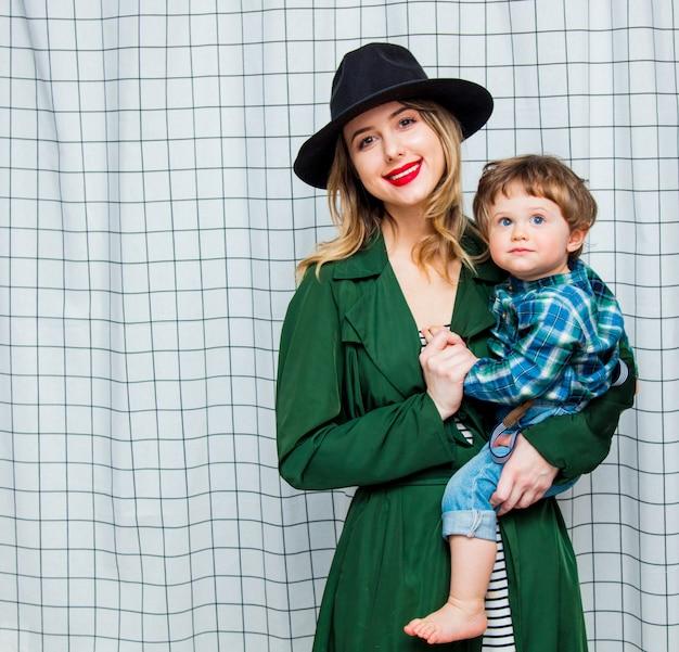 Frau mit hut und grünem mantel im stil der 90er jahre mit kleinkindjungen