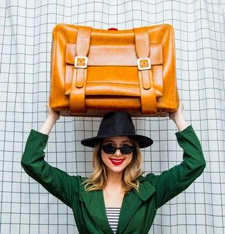 Frau mit hut und grünem umhang im 90er-jahre-stil mit reisekoffer